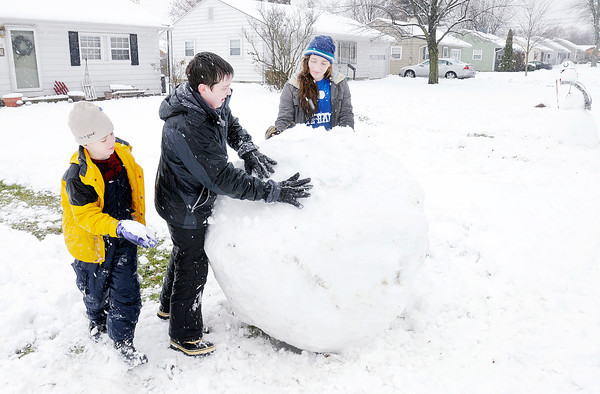 Don Knight / The Herald Bulletin<br /> From left, Joseph, Jonathon and Faith Culp build a giant snowman in their front yard during Saturday's snowstorm.