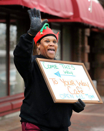 """THB photo/John P. Cleary<br /> Jenneice Kendrick, of the Your Way Cafe, waves and greets people with a """"Merry Christmas"""" as she walks along Meridian Street Friday evening encouraging folks to stop by during Anderson's Winterfest."""