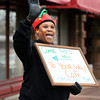 "THB photo/John P. Cleary<br /> Jenneice Kendrick, of the Your Way Cafe, waves and greets people with a ""Merry Christmas"" as she walks along Meridian Street Friday evening encouraging folks to stop by during Anderson's Winterfest."