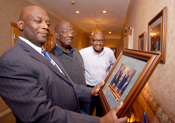 Stan May, his father L.C. May, and brother Ron May look at a family photo that is on display at the family business, L.C. May Funeral Services.