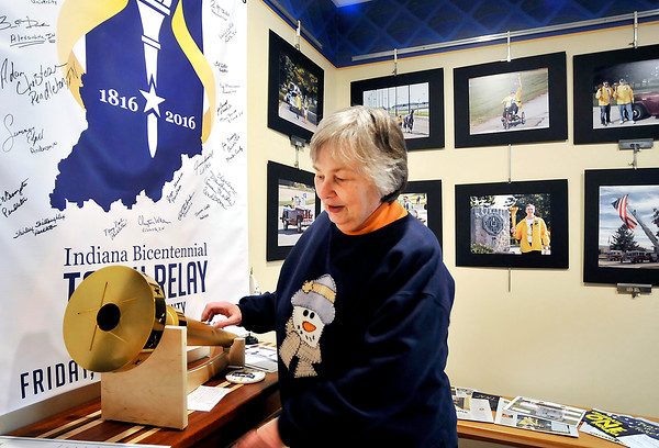John P. Cleary |  The Herald Bulletin<br /> Nancy Noel, Pendleton, looks over the torch she helped carry across Madison County as a torchbearer during the Indiana Bicentennial torch relay October 14th. This is part of a Torch Relay exhibit that opened Thursday at the Anderson/Madison County Visitors Bureau during a holiday reception for all the county torchbearers.