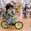 Don Knight | The Herald Bulletin<br /> Madison County reserve officer Ed Bigoss helps Jacob Allen, 7, pick out a bike at Walmart during Cops & Kids program on Wednesday.