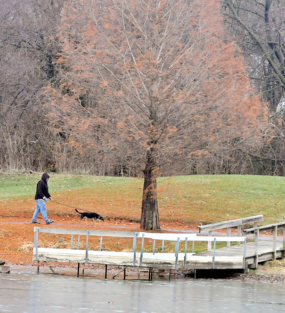 John P. Cleary |  The Herald Bulletin<br /> A blanket of rust colored needles cover the trail as this man walks his dog around the pond at Pulaski Park enjoying the day. Temperatures are forecast to stay seasonable into the weekend.