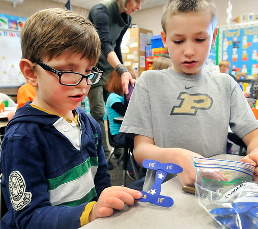 John P. Cleary |  The Herald Bulletin<br /> Lapel Elementary pre-schooler Henry Lacey puts his Indiana Bicentennial ornament in the bag as 4th grader Parker Bannon holds it open for him. The 4th graders will put on ribbons and a hanger so the kids can hang their hand-made ornament on their tree. The Lapel students have been celebrating the state's 200th birthday the past week.