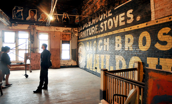John P. Cleary | The Herald Bulletin The A Town Center being developed downtown Anderson by Levi Rinker and Sonia Caldwell. Stripping down the walls of the second floor uncovered this old sign painted on the old brick walls that they refurbished.