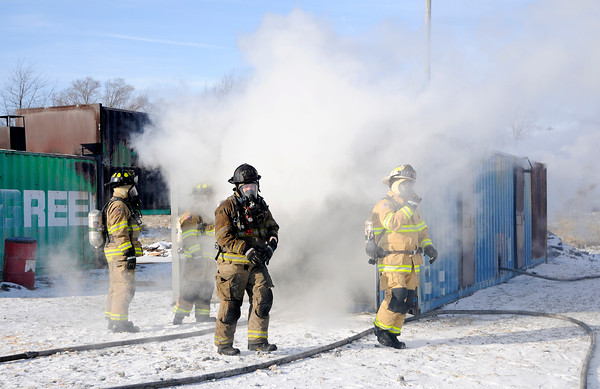 Don Knight   The Herald Bulletin<br /> From left, Shawn Williams, Bob Bennett, health and safety chief Mark Keck and A shift Battalion Chief Ken Helpling exit a shipping container modified to simulate a hallway with bedrooms during training at the Region 6 Fire Training Facility in Anderson on Tuesday.