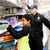 Don Knight | The Herald Bulletin<br /> Evan Henry, 12, finds a long board he wants while shopping with Lapel police officer Dustin Yancy-Ferrell during APD's Cops & Kids program at Walmart on Wednesday. Each kid had $100 to spend on gifts for Christmas.