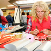 Don Knight | The Herald Bulletin<br /> Beth Hueston ties a ribbon around a gift box during the Season of Giving Gift Fair at the Mounds Mall on Saturday. The event gives people the opportunity to make a donation to a local nonprofit in some ones name as a gift. The event is sponsored by the Leadership Academy of Madison County and showcased 17 local nonprofits.