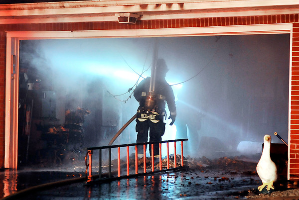 John P. Cleary    The Herald Bulletin<br /> House fire at the corner of Iroquois Street and North Scatterfield Road. Firefighters work their way through the garage to get to the attic  while battling this fire.