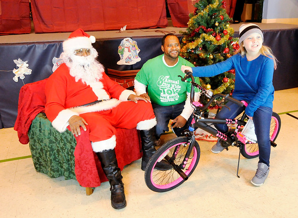 Don Knight | The Herald Bulletin<br /> Kate Fleetwood, 10, gets her photo taken with Santa and Lindsay Brown after receiving a bicycle at the City Wide Toy Give-A-Way at the UAW on Saturday.