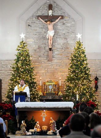 Don Knight   The Herald Bulletin<br /> Father Dan Duff leads a Christmas Eve mass at St. Mary's in Alexandria on Saturday afternoon.
