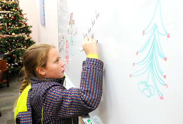 Don Knight | The Herald Bulletin<br /> Diamond Barrett, 11, writes a Christmas message on a white board during the Madison County Community Health Center's annual toy give away on Wednesday.