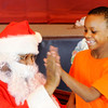 Don Knight | The Herald Bulletin<br /> Dominic Redman, 8, high fives Santa during the City Wide Toy Give-A-Way at the UAW on Saturday.