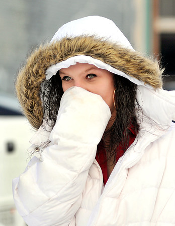 John P. Cleary |  The Herald Bulletin<br /> Charity Elrod, of Anderson, covers her face from the cold temperatures as she leaves work Wednesday evening. A wind-chill advisory has been issued for our area through Thursday morning as temperatures drop to the single digits with gusty winds.