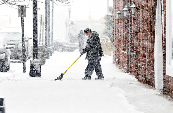 John P. Cleary |  The Herald Bulletin<br /> People were busy cleaning the sidewalks along the businesses on Meridian Street in downtown Anderson as snow developed and moved through the area Wednesday morning.