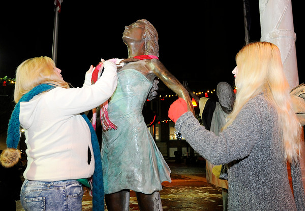 "Don Knight | The Herald Bulletin<br /> From left, Julie and Ariana Asberry place a scarf and gloves on one of ""The Graces"" statues at Dickmann Town Center on Thursday."