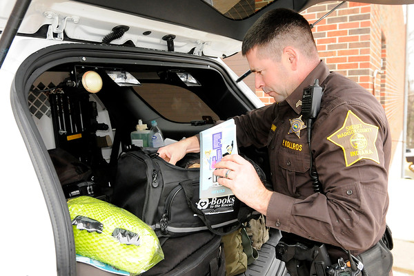 Don Knight | The Herald Bulletin<br /> Paul Kollros has a bag of books and stuffed animals provided by the national Books to the Rescue program. The items were given to officers to use to comfort children in crisis situations.