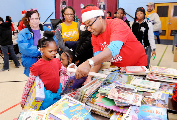 Don Knight | The Herald Bulletin<br /> Volunteer Rodney Nichols helps Jerna Elliott, 8, pick out two books during the City Wide Toy Give-A-Way at the UAW on Saturday.