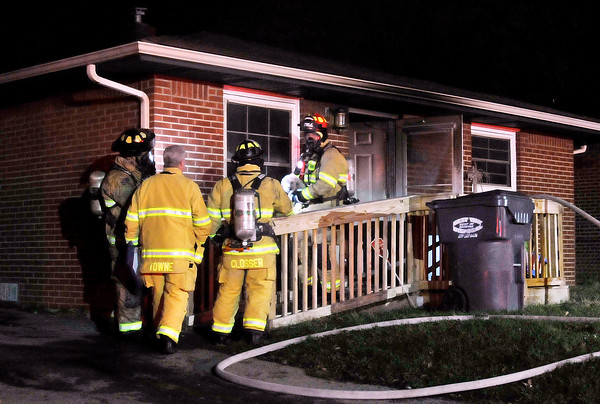 John P. Cleary |  The Herald Bulletin<br /> An Anderson firefighter brings out a cat he found hiding in this house fire in the 3700 block of St. Charles Street Tuesday night. Several animals were rescued from the fire.