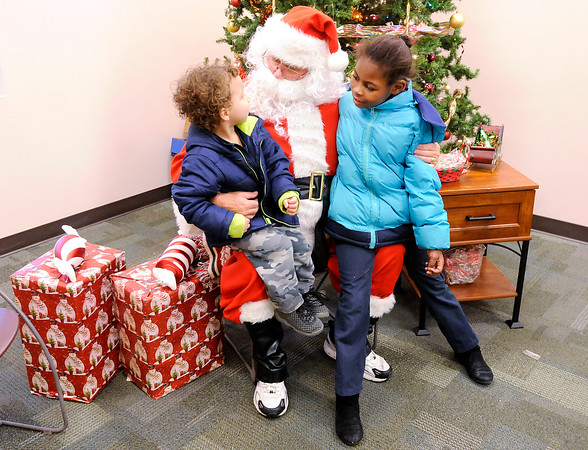Don Knight   The Herald Bulletin<br /> From left, Terrel Perry and Nicole Bybee tell Santa what they want for Christmas during the Madison County Community Health Center's annual toy give away on Wednesday.