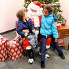 Don Knight | The Herald Bulletin<br /> From left, Terrel Perry and Nicole Bybee tell Santa what they want for Christmas during the Madison County Community Health Center's annual toy give away on Wednesday.