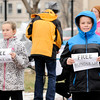 "Don Knight | The Herald Bulletin<br /> Gloria Richardson and Kaleb Day hold up signs during a Bundle Up event inspired by Israelle ""Izzy"" Mattocks. Within the space of an hour all the bundles of warm clothing, blankets and gift cards were distributed in downtown Anderson."