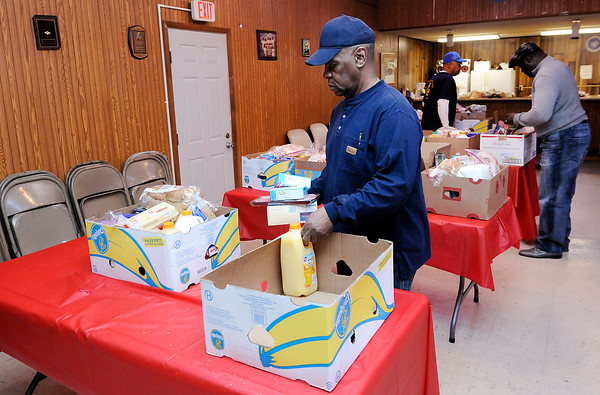 Don Knight | The Herald Bulletin<br /> From left, Clarence Walker, Calvin Green and John Graves Senior fill food baskets for 40 families Peerless Lodge #32 on Friday. Meijer, Strong's Market and Pay-Less donated toward the effort which provides families with a breakfast, lunch and dinner for Christmas Day.