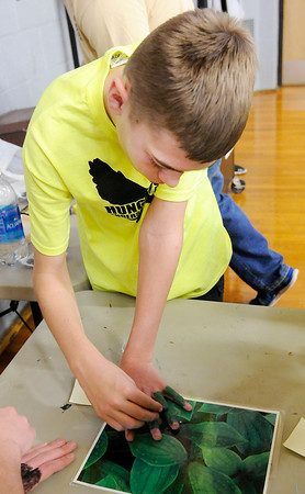 Don Knight | The Herald Bulletin<br /> Austin Holtzman, 16, camouflages his hand during Hunger Games Day at APA on Wednesday.