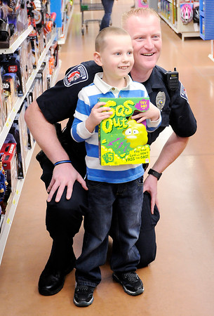 Don Knight | The Herald Bulletin<br /> APD officer C.J. Christian poses for a photo with Zander McCormick, 5, after helping him pick out toys during APD's Cops & Kids program at Walmart on Wednesday.