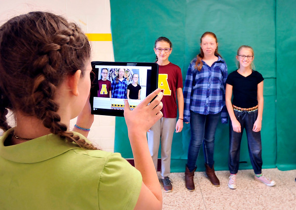 John P. Cleary |  The Herald Bulletin<br /> Alexandria Intermediate School 6th graders from Shannon Howell's class video a segment for the school announcements in the hallway. Rachel Waldroup uses the iPad to shoot as Lilly Thomas, Madison Carver, and Katy Stillwell go through their lines for the camera.<br /> <br /> <br /> <br /> their video projects for school announcements.