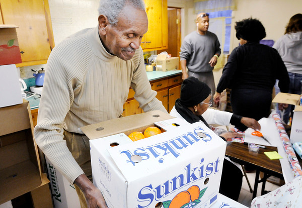 Don Knight | The Herald Bulletin<br /> Johnny Wilson moves a box of oranges as volunteers prepare holiday food baskets on Friday for Allen Chapel AME's Christmas Give-a-way. The Give-a-way was held on Saturday and was made possible by proceeds from events around the dedication of Wilson's statue at Anderson High School this summer.