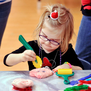 John P. Cleary |  The Herald Bulletin Kylie Scott, 4, gets into making her play dough cookie, with eyes, during the Anderson Public Library's annual Toddler Tango/Preschool Promenade holiday special Tuesday. The event will be held again this Thursday morning from 10:30 a.m. to noon featuring stories, songs, snacks and making festive keepsakes.