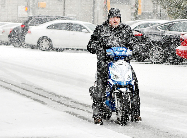 John P. Cleary |  The Herald Bulletin<br /> This guy uses his feet for balance as he slowly rides his mopad along East 10th Street as snow was falling making road conditions slick and hazardous Wednesday morning.
