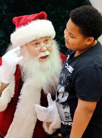 "Don Knight |  The Herald Bulletin<br /> Santa talks to Jalen Berry, 9, at the Mounds Mall on Saturday. Michael ""Wolfie"" Davis portrayed Santa at the mall this season."
