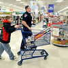 John P. Cleary |  The Herald Bulletin<br /> Anderson FOP provided Christmas for 80 children during their annual Shop With A Cop program at Meijer's. Anderson Police officer Spencer Pettit assists Dakota Garman, 9, as they wheel their cart through Meijer's Tuesday morning.