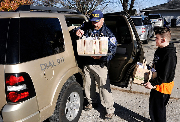 Don Knight    The Herald Bulletin<br /> L.G. Gentry holds a tray of baked goods as Markleville Police Chief Tim Basey loads his suv as he helps Michelle Hoppes with deliveries of baked goods around town on Saturday. Hoppes started a Facebook bake sale to help her sister who lost her job due to an illness.