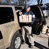 Don Knight |  The Herald Bulletin<br /> L.G. Gentry holds a tray of baked goods as Markleville Police Chief Tim Basey loads his suv as he helps Michelle Hoppes with deliveries of baked goods around town on Saturday. Hoppes started a Facebook bake sale to help her sister who lost her job due to an illness.