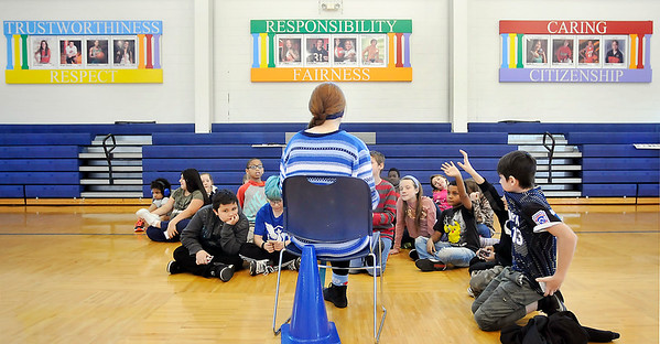 John P. Cleary |  The Herald Bulletin<br /> The six pillars of character are on the gym wall at Erskine Elementary School as Megan Moran, a Anderson High School volleyball player and Athletes of Character, talks to fifth-graders Friday about each of the pillars.