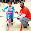 Don Knight |  The Herald Bulletin<br /> Cariel Hendricks, 4, poses for a photo with her new bike after it was presented to her by Lindsay Brown during the City Wide Toy Giveaway at the UAW on Saturday.