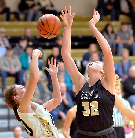 John P. Cleary |  The Herald Bulletin<br /> Madison-Grant's Zoey Barnett and Lapel's Breanna Boles try to grab the loose ball.