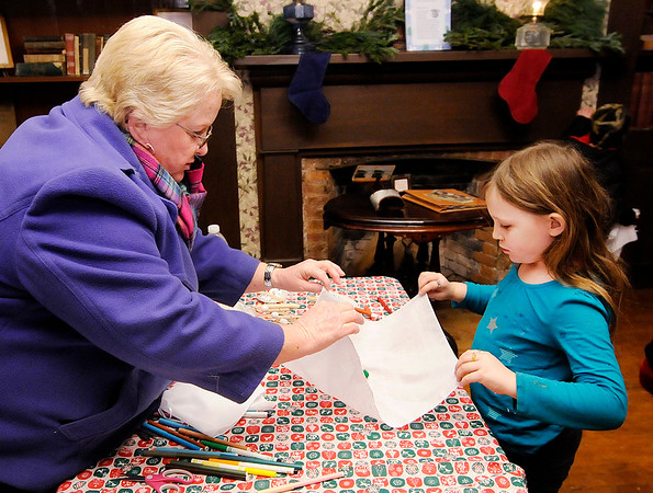 Don Knight |  The Herald Bulletin<br /> Sharon Dailey helps Ellie Hoover, 7, make an angel ornament during Christmas at the Bronnenberg Home at Mounds State Park on Saturday.
