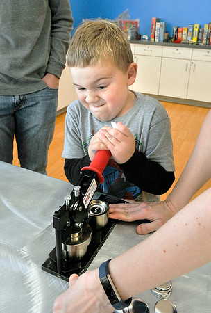 John P. Cleary |  The Herald Bulletin<br /> Collin Forster, 7, strains as he pulls down the handle on a button maker as he attended the Holiday Boredom Busters event at the Anderson Public Library Wednesday afternoon. The library held the event to break the holiday boredom with games, crafts, and fun.