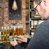 John P. Cleary |  The Herald Bulletin<br /> Zach Willard puts labels on bottles of Limonchello Liqueur at Oakley Brothers Distillery Tuesday as they have opened to sell their spirits by the bottle for the holidays ahead of their official opening.