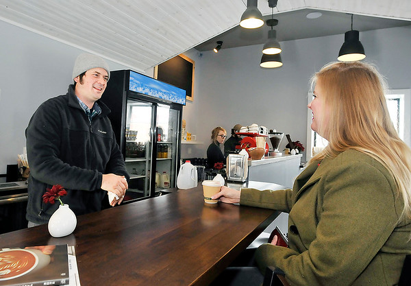 John P. Cleary |  The Herald Bulletin<br /> Jackrabbit Coffee co-owner Josh Stafford talks with customer Sarah Price Thursday on their first day being open for business. Stafford purchased the former Hot Dog Circus building at John and 11th Streets and teamed with Ben Orcutt to open the coffee shop.
