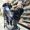 John P. Cleary |  The Herald Bulletin<br /> Carson Edmonds, 2, excitedly scans the shelves as he is being pushed by Anderson Police officer CJ Christian during Anderson FOP's annual Shop With A Cop program Tuesday morning at Meijer's.