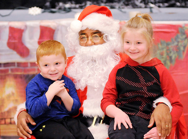 Don Knight |  The Herald Bulletin<br /> From left, Lucas and Zoy Burns pose for a photo with Santa during the City Wide Toy Giveaway at the UAW on Saturday.