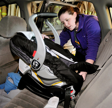 John P. Cleary |  The Herald Bulletin<br /> Amanda Arnold, of Safe Kids, secures a car seat to it's base after inspecting the unit for proper installation during a safety inspection last week.