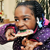 John P. Cleary |  The Herald Bulletin<br /> Shawnnee Perry, 4, reaps the benefit of her cookie decorating by getting to eat it while visiting the Soroptimists' Celebrity Cookie Walk Friday.