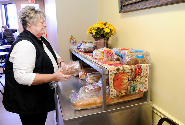 Don Knight |  The Herald Bulletin<br /> Ann Bousman sets out loafs of bread as she volunteers at The Christian Center on Tuesday.
