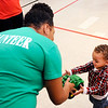 Don Knight |  The Herald Bulletin<br /> Volunteer Alyssa McCutchen gives a toy tractor to Clayton Coffey, 2, during the City Wide Toy Giveaway at the UAW on Saturday.